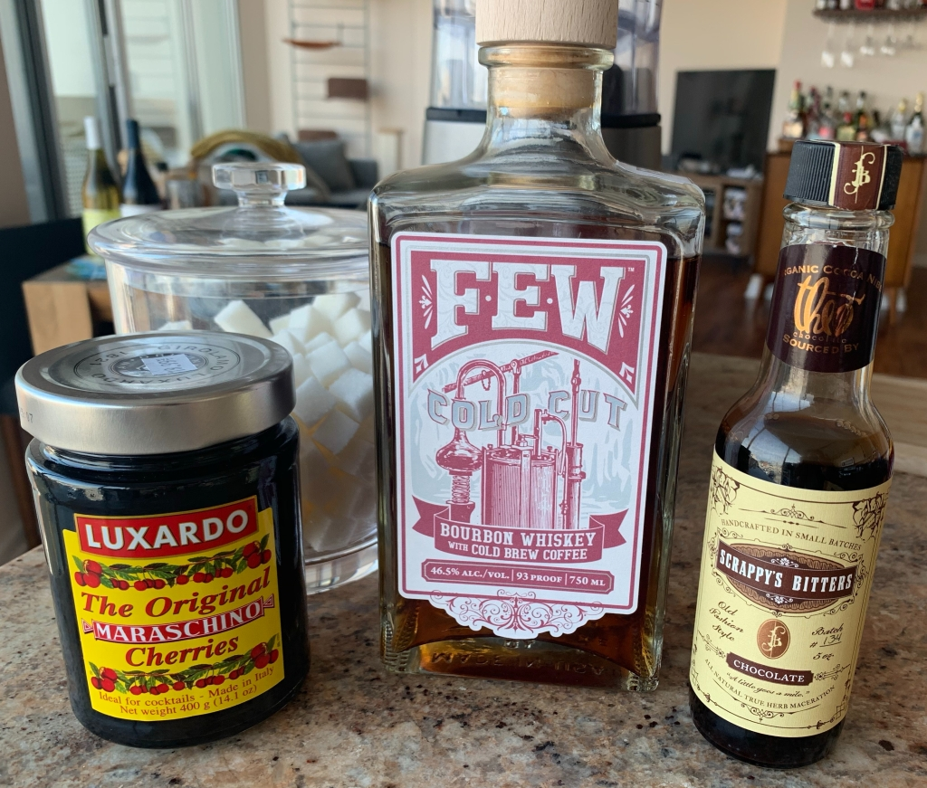 FEW cold-cut bourbon, chocolate bitters from Scrappy's Bitters, a jar of Luxardo maraschino cherries, and a jar of sugar cubes.